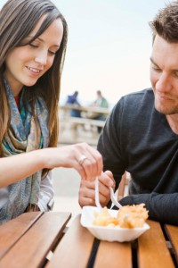 Couple eating fish and chips outdoors