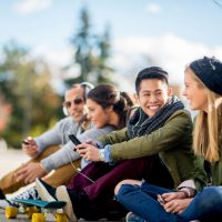 A multi-ethnic group of college age students are sitting together texting on their cell phones and taking selfies together.